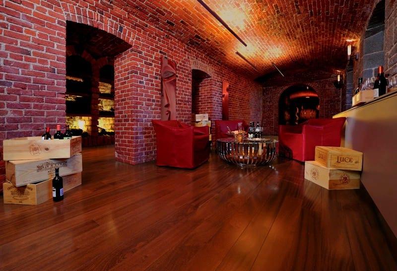 wohnidee für luxus wohnzimmer und Weinkeller mit Holzboden und Ziegelmauern