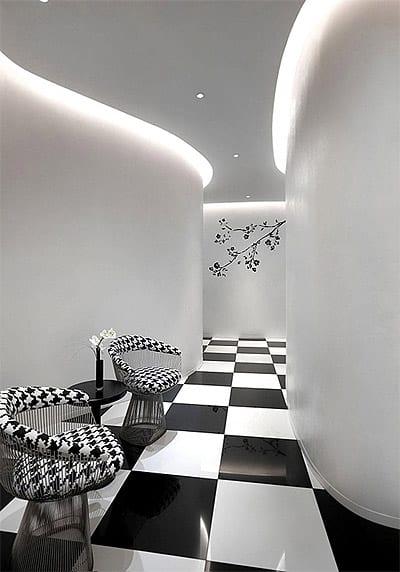 moderne Raumgestaltung und minimalistisches Interior mit schwarz-weiße bodenfliesen und sesseln