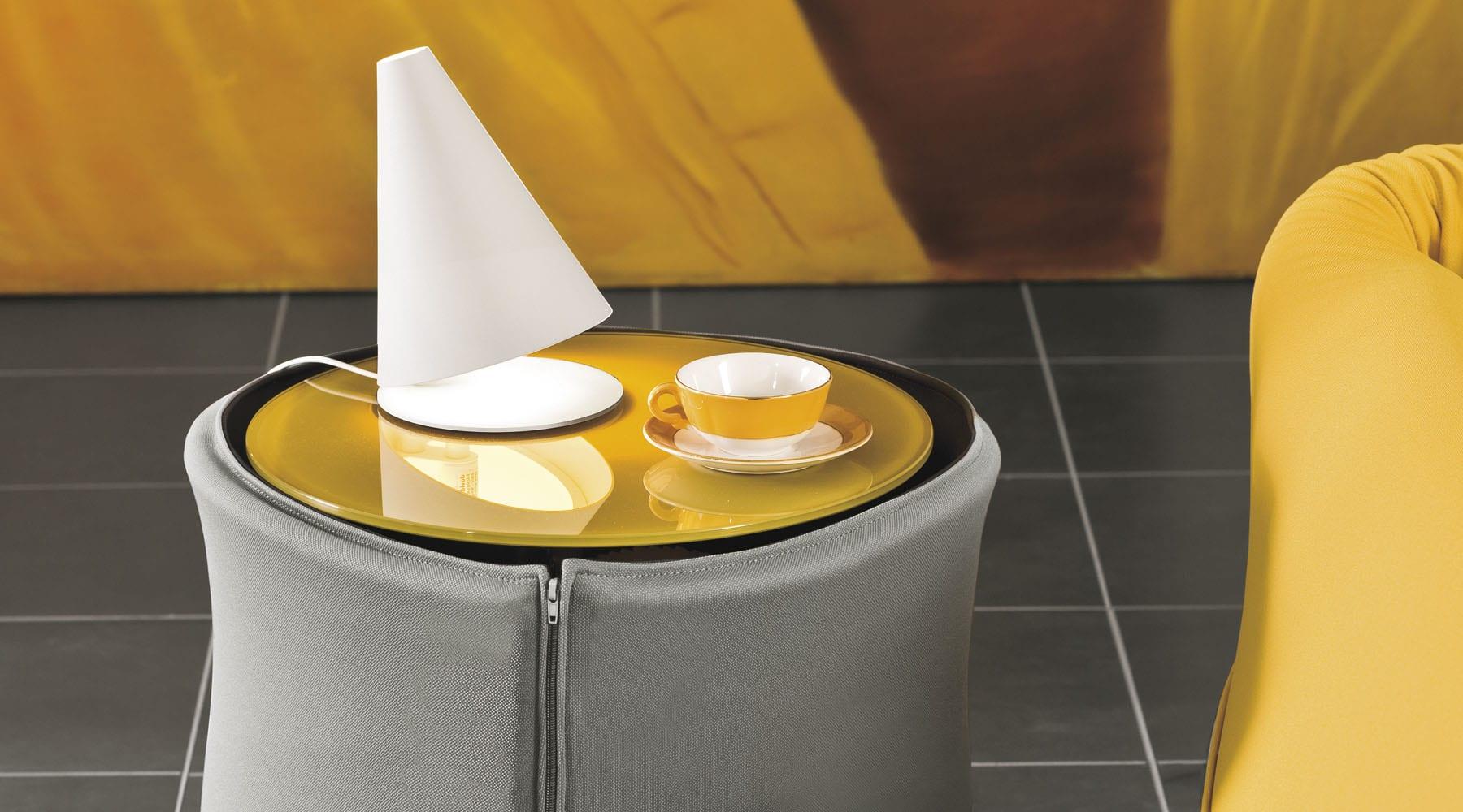 runder beistelltisch und nachttisch mit gelben glascheibe und grauer Stoffhülle für modernes Interior design in gelb und grau