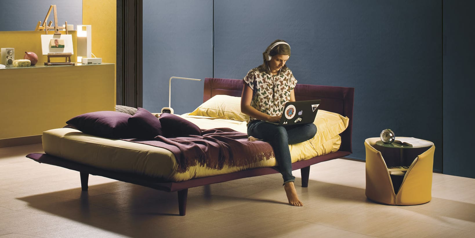 moderne schlafzimmer in gelb und blau mit nachttisch gelb und bett in lillafarbe