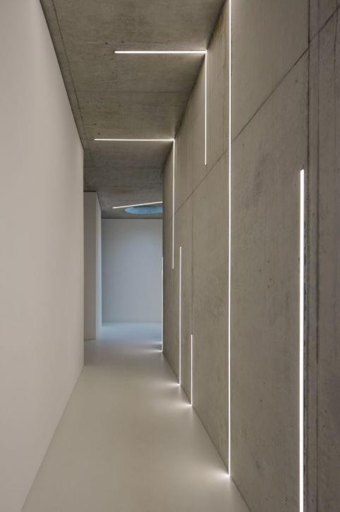 minimalistisch wohnen_wohnidee flur aus beton mit eingebauten Lichtspalten als wand- und deckenleuchten