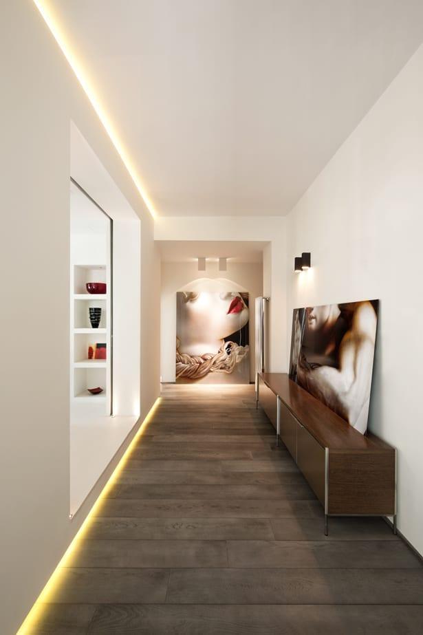 moderne flurbeleuchtung mit indirekter wandbeleuchtung und modernes interieur design in weiß mit holzboden und sideboard holz mit bilderrahmen dekoriert