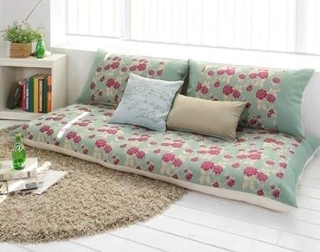 wohnzimmer mit holzbodn weiß und coole sofa desin in weiß und grün mit rosablumen