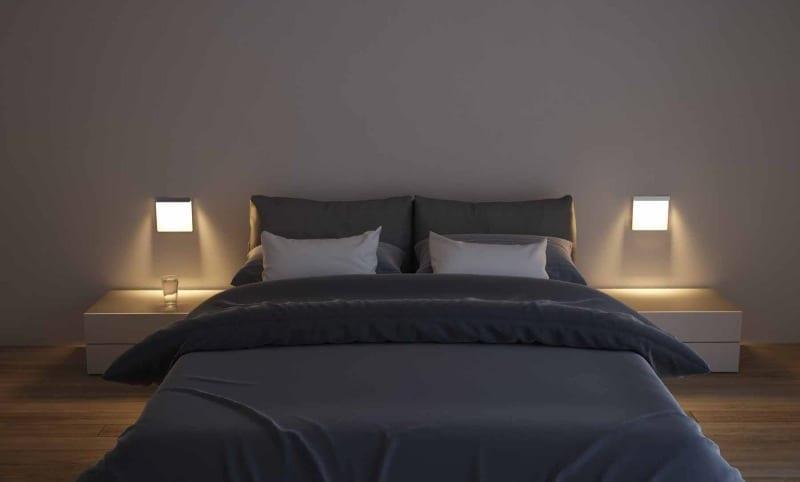 schlafzimmer einrichten mit weißen nachttischen und wandleuchten und moderne bettwäsche schwarz