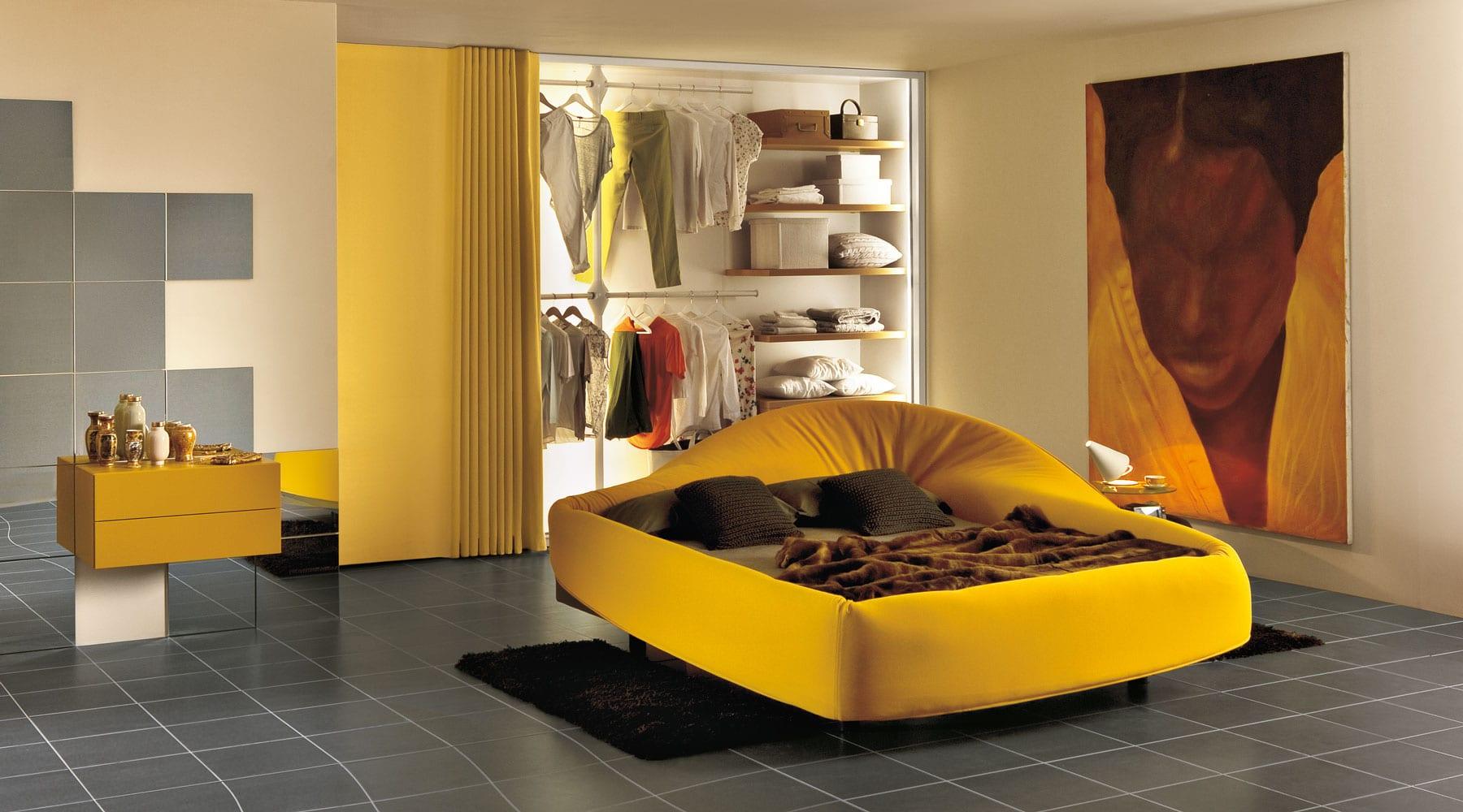 kreative schlafyimmer gestaltung mit gelben bett und nachttisch und modernes Kleiderschrankszstem mit schiebbarer Stoffbahn