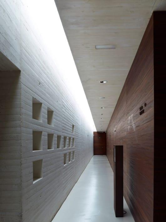 minimalistisches interior mit sichtbeton und holzverkleidung für den flur und Flurbeleuchtung mit tageslicht über glasdach