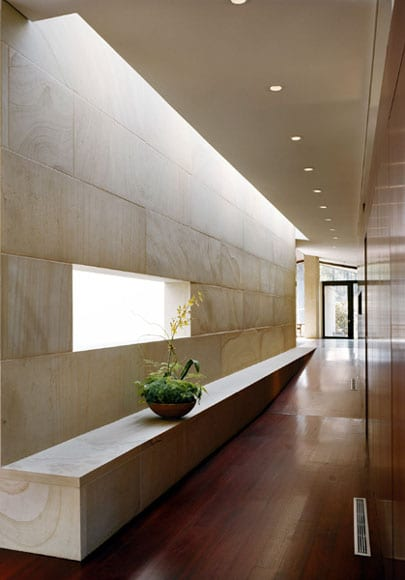 korridor mit rampe und indirekte wandbeleuchtung durch wandnische in natursteinwand_lichtakzent durch oberlicht  über sideboard flur