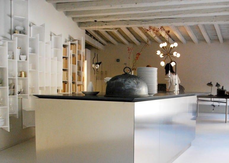 weiße küchen-wandregale von boffi für moderne kücheneinrichtung mit weißer küche und kochinsel mit schwarzer  Küchenarbeitsplatte