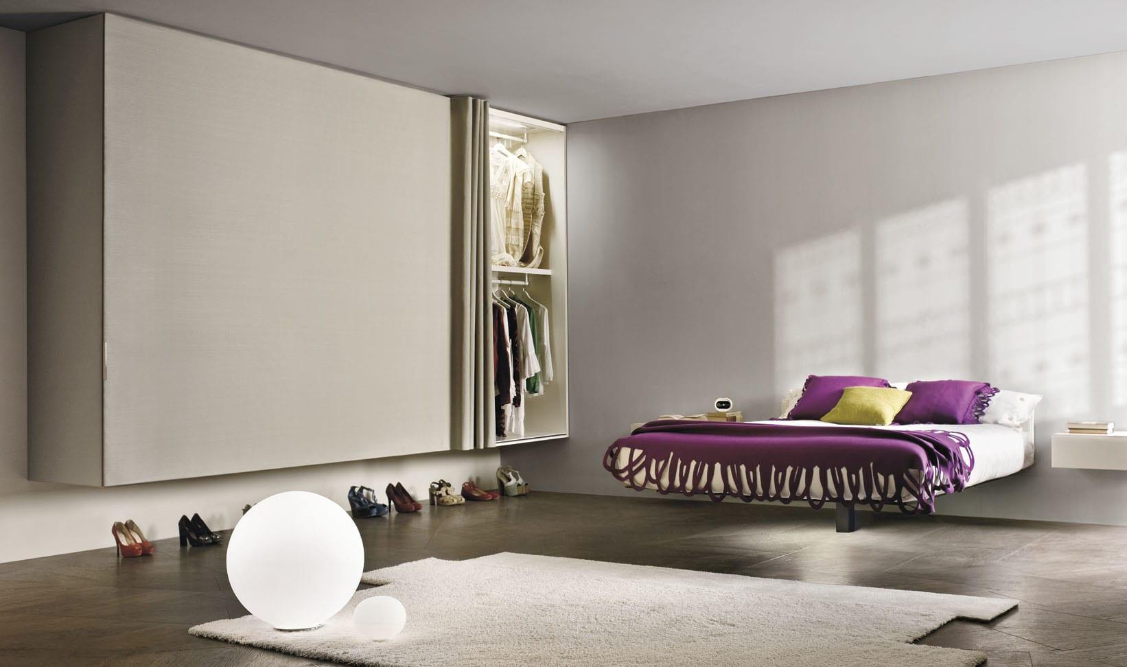 minimalistische schlafzimmer interieur in weiß mit modernem Wandschrank und schwebendes Bett mit bettdecke lila
