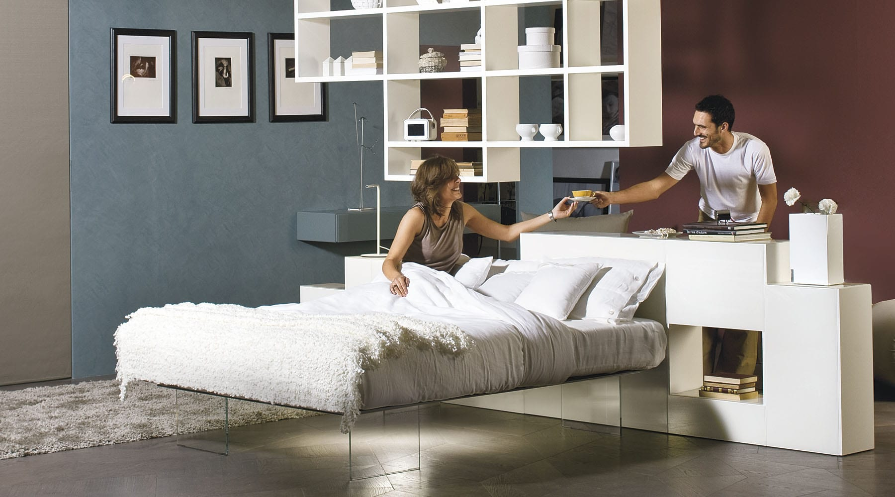 kleines wohnzimmer mit bett und modernen weißen Regalen als Raumtrennug und wandfarbe blau und lilla
