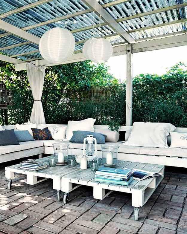gartenterrasse mit Pergola Terrassenüberdachung in weiß mit weißen gardinen und Kugel-Pendellampen und Gartenmöbel aus paletten