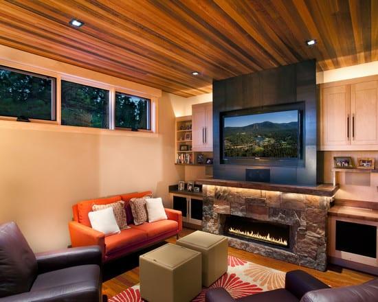 kleines wohnzimmer mit holzdecke und kamin aus naturstein mit tv Wandpaneel schwarz