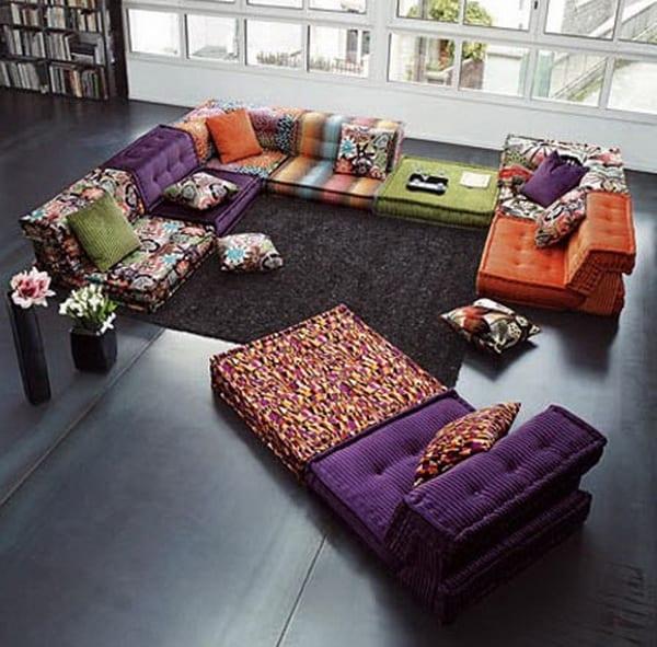minimalistisches interior mit boden schwarz und sitzecke mit bunten bodenkissen und teppich schwarz