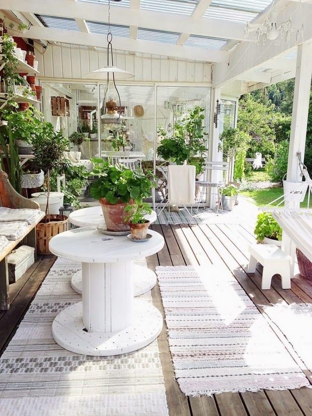 holzterrasse mit terrassenüberdachung aus glas und holz und terassendeko mit wandregalen und  gartenbank holz