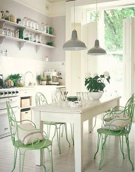 weiße küche mit wandregalen, metall-pendellampen und holztisch in weiß und Farbakzent in hellgrün