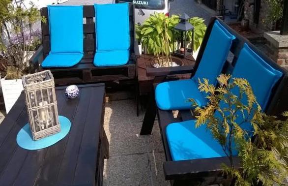 terrasse einrichten mit DIY Terrassenmöbel aus Paletten in schwarz mit blauen Sitzkissen dekorieren