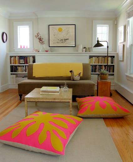 kleine wohnzimmer einrichtung mit sofa in beige und bodenkissen in gelb und pink