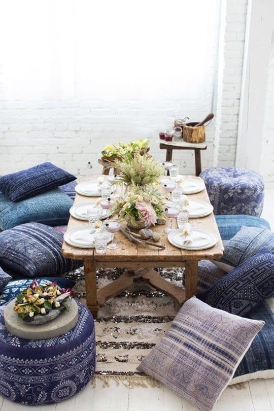 rustikale couchtisch holz mit blauen bodenkissen arangieren