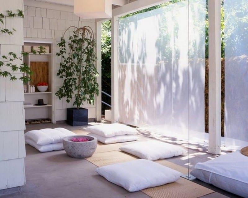 überdachte terrasse einrichtung mit weißen bodenkissen und gardinen