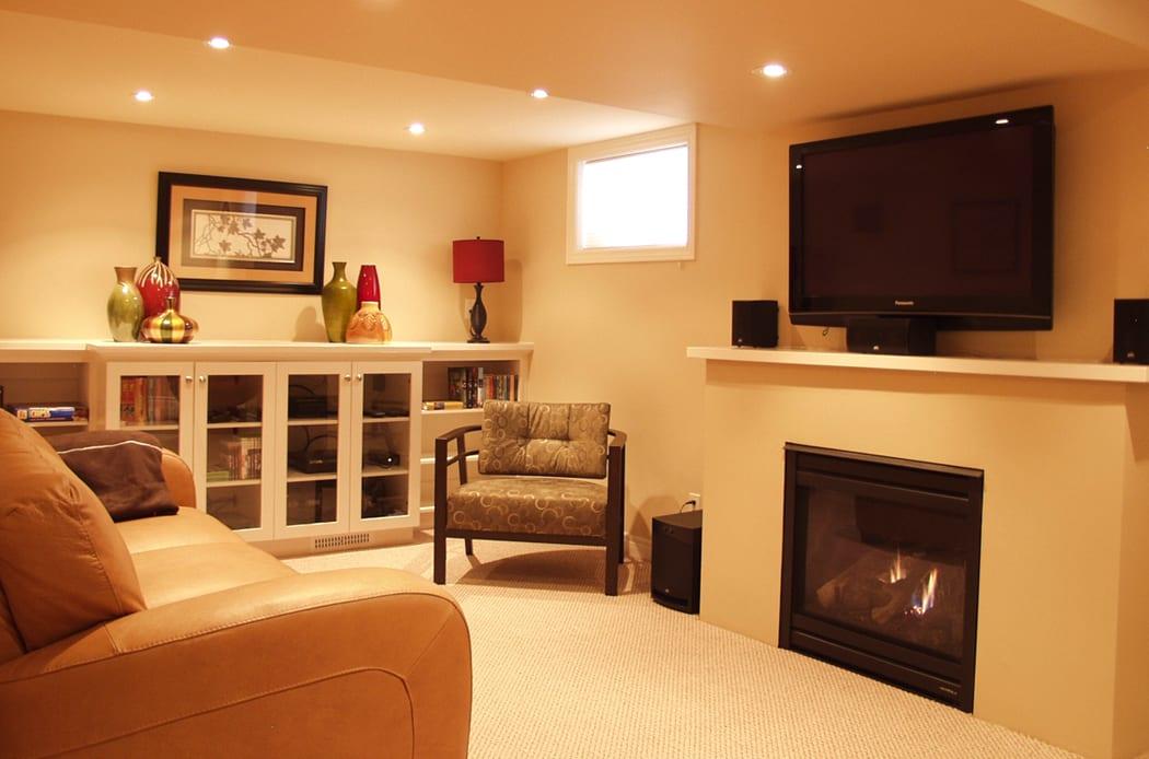 keller wohnzimmer idee fr moderne wohnzimmereinrichtung mit ledersessel braun und tv ber dem kamin - Wohnzimmer Ideen Mit Kamin