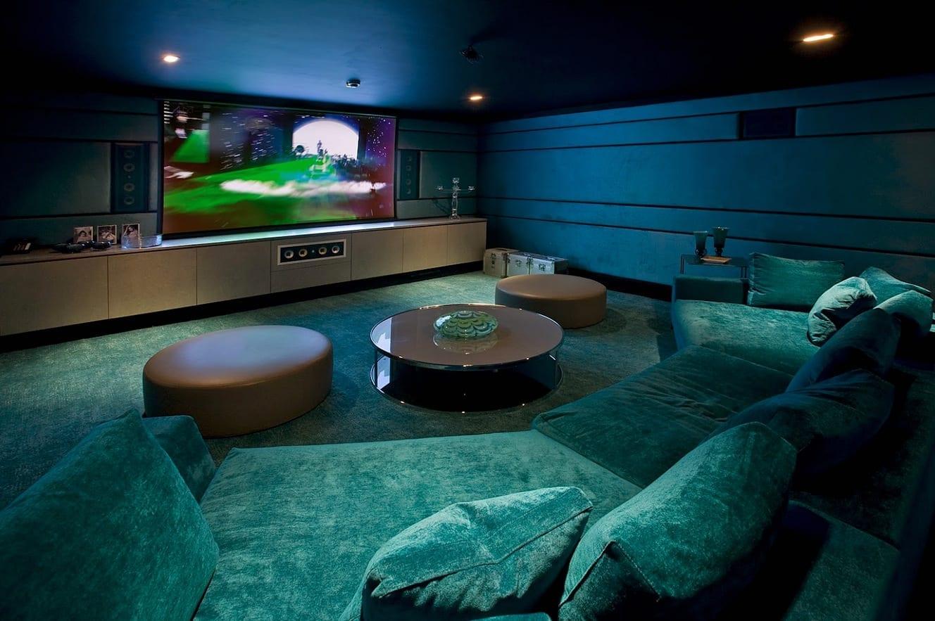 luxus wohnzimmer mit blauer decke und Sofa blau mit runden lederhockern und runder Couchtisch aus Glas