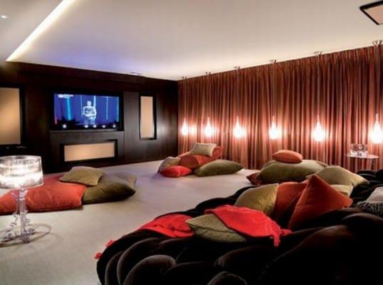 coole idee für keller einrichtung als mediaraum mit tv wandpaneel und bodenkissen in grün und rot