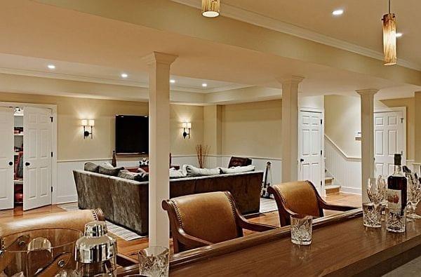 luxus wohnzimmer im keller mit wandfarbe beige und Bar mit Holztheke und Barhockern aus holz und leder