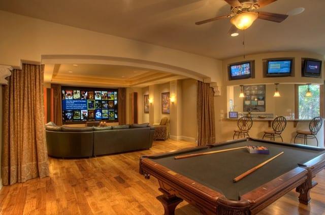 moderne wohnzimmer einrichtung mit Billardtisch und TV Wandpaneel vor Ledersofa grün
