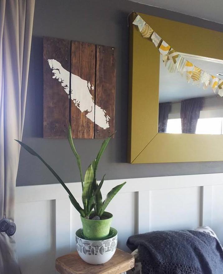 coole wanddeko idee mit Palettenbild und Wandspielegel mit gerbem Holzrahmen als Farbakzent zu der Wandfarbe grau