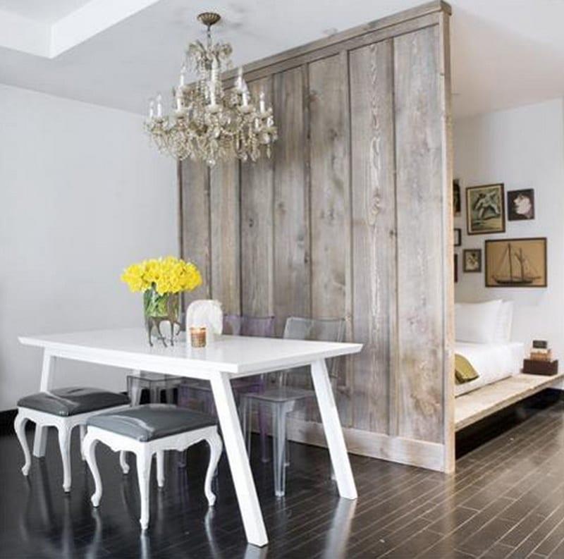 kleine wohnzimmer idee mit holzboden schwarz und Holztrennwand zwischen wohn- und schlafbereich mit weißem Esstisch holz und barok-hocker weiß mit polstersitz in lack grau