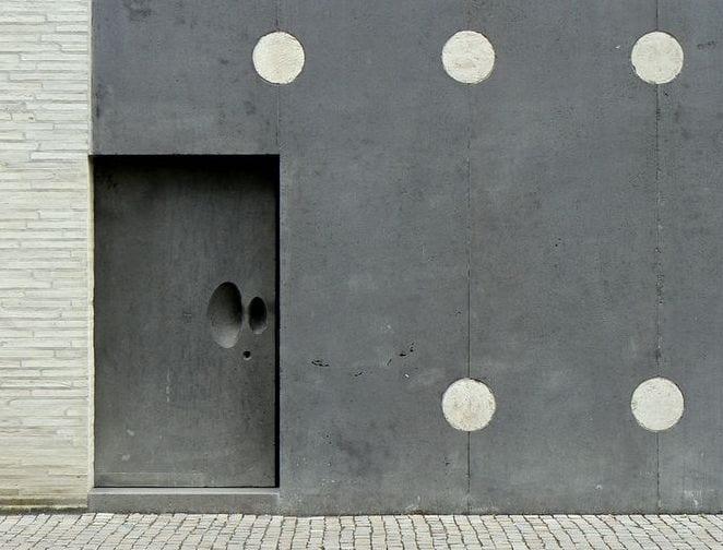 moderne fassade aus schwarzem basalt mit massiver eingangstür aus naturstein schwarz