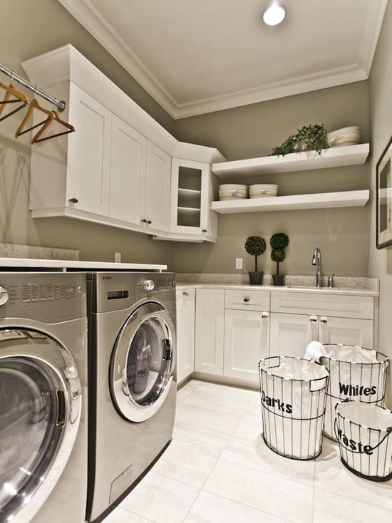 interessante waschküche-einrichtungsidee mit kreativen wäschekörben und inox waschmaschine und weißen wandschränken und wandregalen aus holz