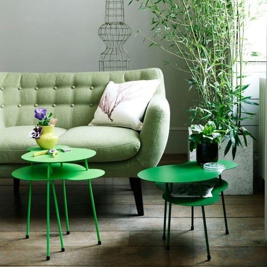 kleine wohnzimmer modern einrichten mit polstersofa in hellgrün und modernen runden Metall-Beistelltischen in grüm