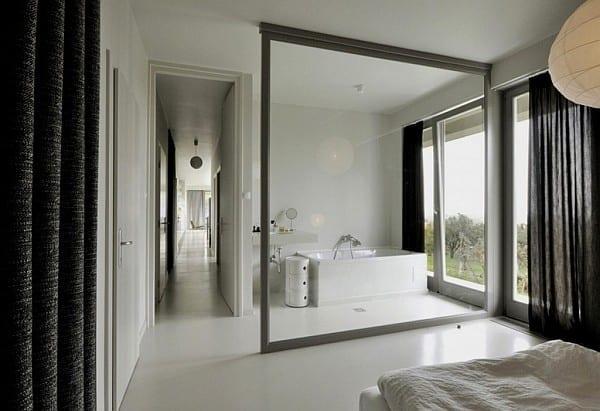 moderne Schlafzimmer mit offenem Badezimmer und schwarzen Gardinen