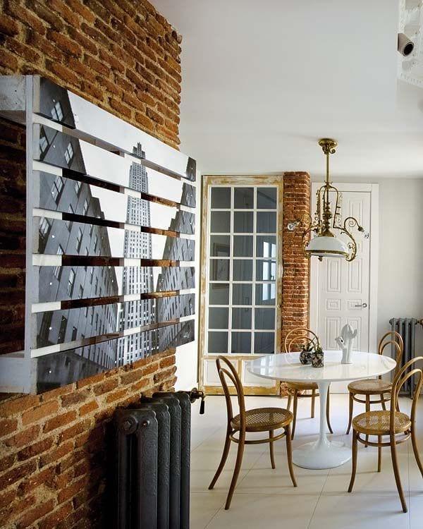 moderne wohnzimmer idee für coole Wandgestaltung einer ziegelwand mit selbstgemachtem Bild aus Paletten_rustikale einrichtungsidee mit weißem esstisch rund und alte holztür mit glas in weiß