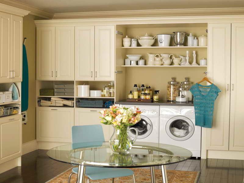 waschküche mit weißen holzschrenken und rindem tisch aus glas