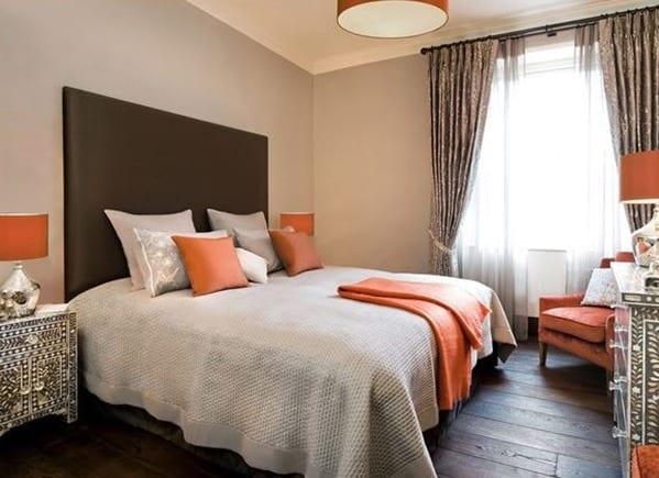 moderne schlafzimmer interior mit hellgrauen wänden und farbgestaltung in orange und grau