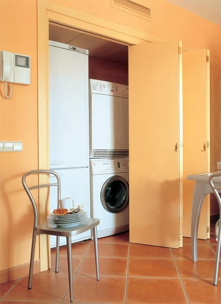 küche farbgestaltung mit der wandfarbe apricot und platzsparende nische mit falttüren für kleine waschküche