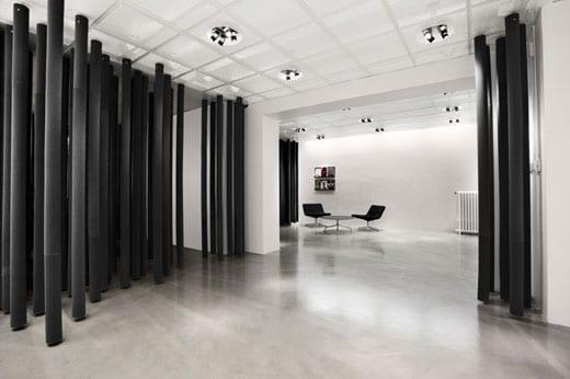 minimalistische einrichtung mit schiebbaren hängenden raumteiler-Zylindern und poliertem betonboden