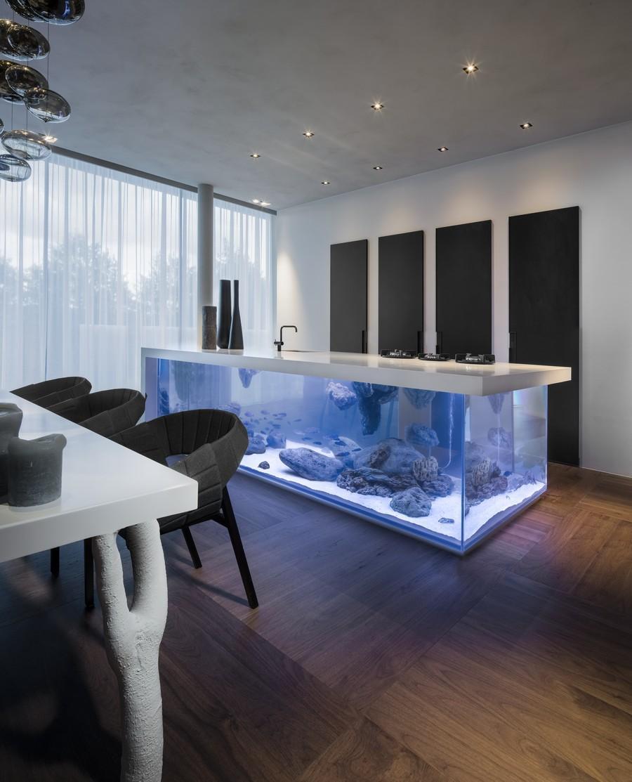 minimalistische küche einrichten mit moderner kochinsel-aquarium und Designer-Esstisch weiß mit schwarzen Armsesseln und coole Wanddekoration küche mit eingebauten Küchenschränken