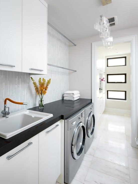 interessante waschküche-einrichtungsidee mit platzparende kleidungständer und eingebauten weißen schränken