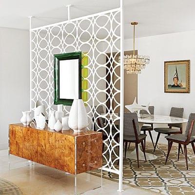 klassisches Sideboard holz mit weißen vasen dekoriert und Raumteiler-Gitterwand weiß mit Spiegel in grünem bilderrahmen dekorieren