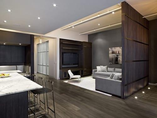 schwarzer holzbodenbelag für moderne wohnzimmergestaltung mit wandfarbe grau und TV wandpaneel und ecksofa grau