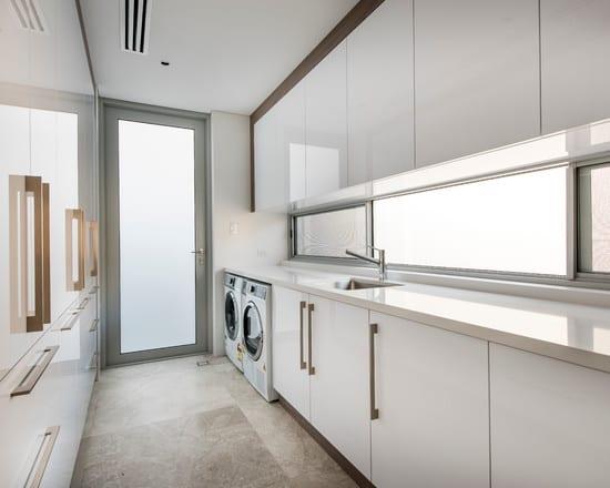 moderne kleine küche weiß mit küchenschränken in glanz-weiß und natursteinboden