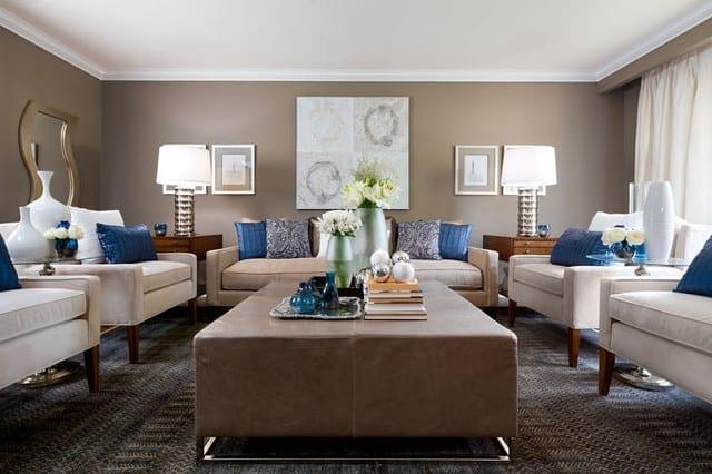 wandfarbe hellbraun als wandfarbe im wohnzimmer mit weißen armsesseln und leder-hocker-tisch in beige