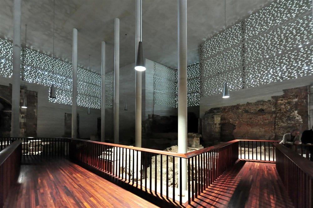 kreatives museum-interior mit holzwegen und runden betonstützen