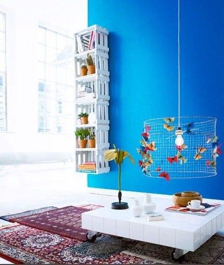 einrichtung wohnzimmer mit couchtisch weiß auf rollen und selbstgebautem Wandregal aus Paletten in weiß