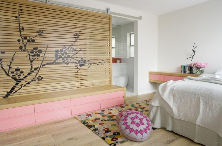 moderne Schlafzimmer einrichtung und wandgestaltung mit Holz-Raumteiler und  Holzschrank mit rosafarbigen schubladen