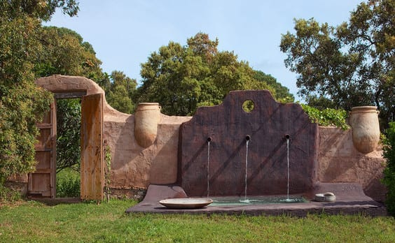 garten einrichten mit betongartenmauer mit ausgemauerten Blumentöpfen und Gartenmauer deko mit Rohrbrunnen