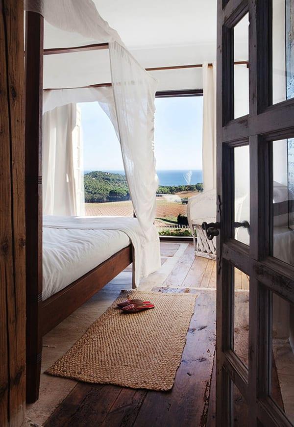 modernes Schlafzimmer mit Holzbett und Baldachin und glasvitrine mit blich aus meer